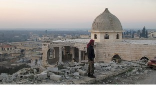 A Free Syrian Army fighter inspects a damaged mosque in Harem town, Idlib Governorate