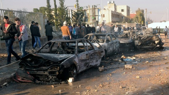 Damaged cars are seen at the site where two explosions rocked the University of Aleppo 