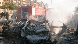Damaged cars are seen at the site where two explosions rocked the University of Aleppo in Syria's second largest city