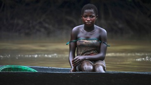 A young woman is pictured coated in oil stains as she sits in a canoe near river Nun in Nigeria's oil state of Bayelsa