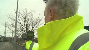 A man pointing a speed monitor