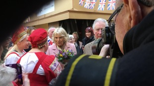 Camilla, Duchess of Cornwall, receives flowers from ladies dressed as Russian dolls