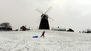 A child walking with a sledge at Whitburn Windmill near Sunderland.