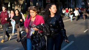 People walk down the center of a street in the Roma neighborhood after an earthquake shook Mexico City, Friday, Feb. 16, 2018.