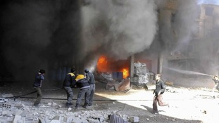 members of the Syrian Civil Defense extinguishing a store during airstrikes in Ghouta,