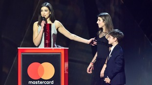 Dua Lipa, with her brother and sister, accepting the award for British Breakthrough on stage at the Brit Awards