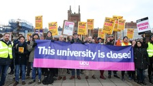 Lecturers stage a strike outside the gates of Queen's University in Belfast.