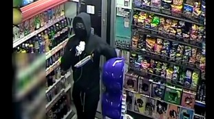 Shocking CCTV of shop-owner threatened with knife before robber gives sweets to mother and child outside