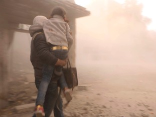 A man carries a girl away from the site of a bombing