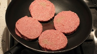 A general view of four beef burgers in a frying pan.