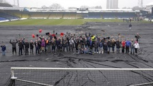 Fans gather for a photo after clearing the pitch at Roots Hall