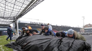 Fans roll back the plastic covering