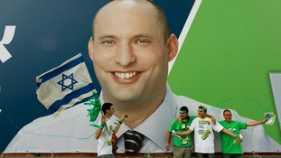 Supporters of the the far-right Jewish Home party stand in front of a campaign poster depicting Naftali Bennett in Tel Aviv.