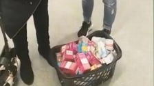 Footage captures the moment two women emptied dozens of items from their 'specially-adapted' coats