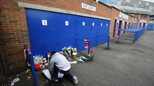 A fan lays tributes at the Leppings Lane End at Hillsborough