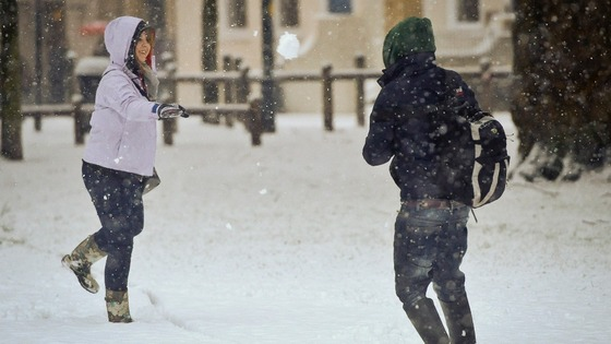 People have a snow ball fight in Bristol as heavy snow disrupts travel and services in the city.