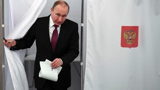 Vladmir Putin exits a polling booth as he prepares to cast his vote in Russia's presidential election