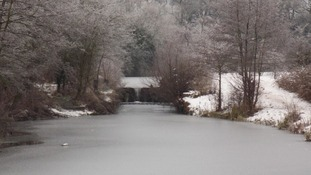 A river in Derbyshire appears frozen after overnight snow.