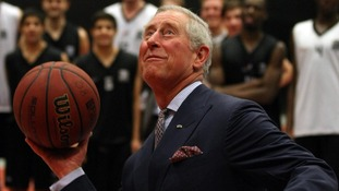 Prince Charles on his visit to Sweden attempting to shoot a hoop while playing basketball.