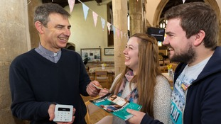 Couple hand their debit card to Vicar