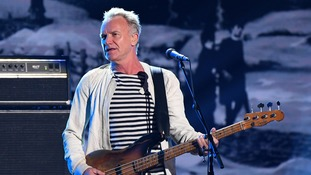 Sting on stage performing with guitar