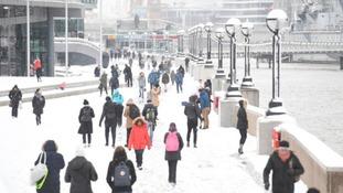 People walking in the snow by Tower Bridge