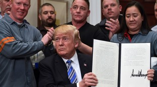 Donald Trump holds up a proclamation on steel and aluminium imports earlier this month