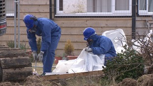 Workers in masks help to clear asbestos from chalets in Hemsby