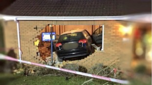 Two hurt after car crashes through house