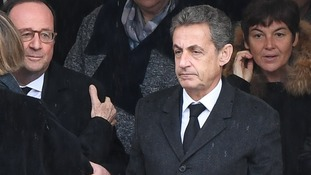 Nicolas Sarkozy, who is accused of corruption, stands with fellow former president François Hollande.