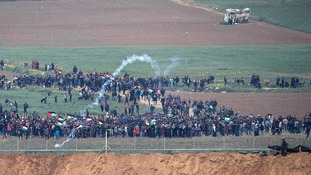 Palestinians gather at the border fence.
