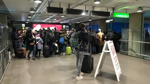 Passengers queue for trains to leave Stansted Airport
