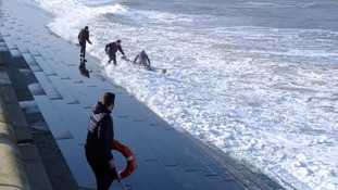 Four people have been rushed to hospital after falling into the sea during a rescue attempt.