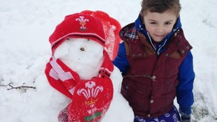 A snowman in Welsh hat and scarf