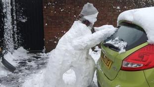 A snowman 'pushing' a car