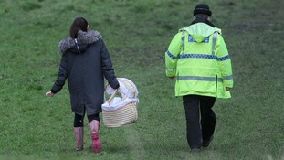 Police were seen carrying a pink moses basket at the field where the body of a newborn baby was found