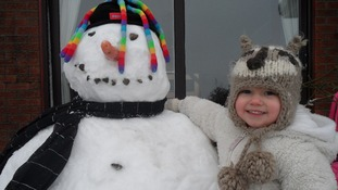 A little girl and her snowman