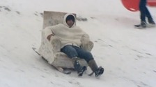 A man speeds down a Norfolk hill in his toboggan armchair.