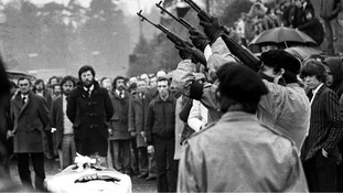 Three masked IRA men fire volleys of rifle shots over a coffin at a republican funeral. Gerry Adams can be seen in background.