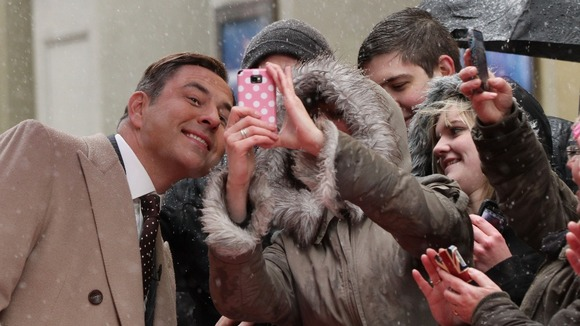 David Walliams poses for pictures with waiting fans.