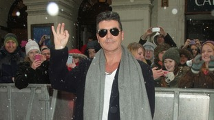Simon Cowell waves for the cameras in London.