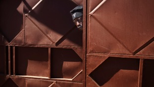 A Malian soldier peeks through a doorway behind where Malian and French soldiers are stationed in Niono.
