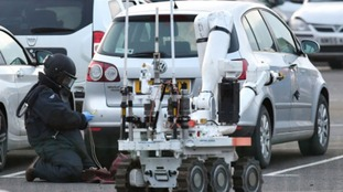 A man in a full bomb disposal suit and helmet was seen looking at a silver Volkswagen Golf