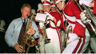 Bill Clinton plays the saxophone with members of the University of Arkansas marching band in 1992