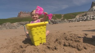 Girl with bucket and spade on beach