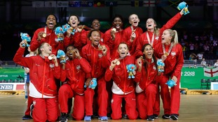 The England women's netball team celebrate with their gold medal