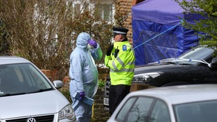 A police officer and a forensic officer outside a house in South Park Crescent in Hither Green, London.