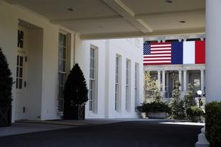 The US and French flags as seen through the portico of the West Wing (Alex Brandon/AP)