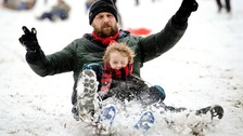 James Sledge and his son Buster have fun sledging in Victoria Park, Totterdown, Bristol