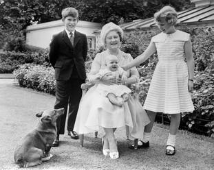 Prince Andrew smiles on the lap of his grandmother, the Queen Mother, as his brother, Prince Charles, and sister, Princess Anne, look on, in the garden of Clarence House, London.